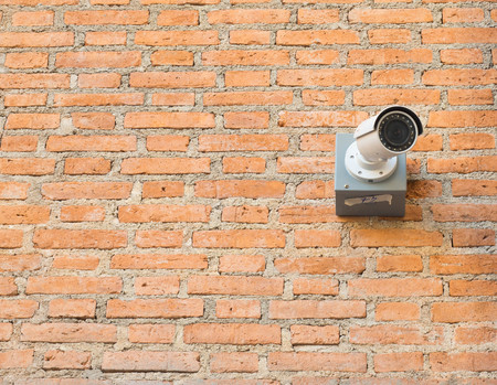 One closed circuit camera on brick wall