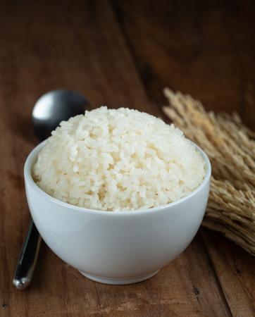 Dampf weißer Reis in weißer Keramikschale auf Holztisch für gesundes Essen. Kochkonzept. Selektiver Fokus.