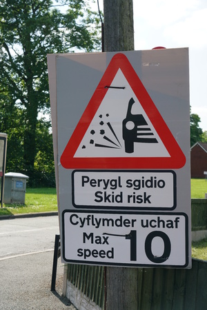 skid: Road sign showing skid risk written in Welsh and English Stock Photo