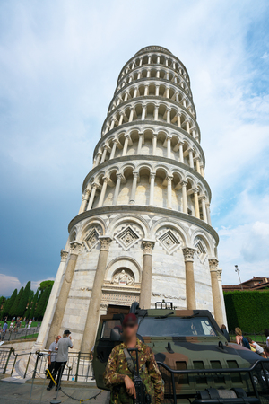 Pisa, Italy-July 26, 2018: Tower of Pisa or leaning tower guarded by soldiers