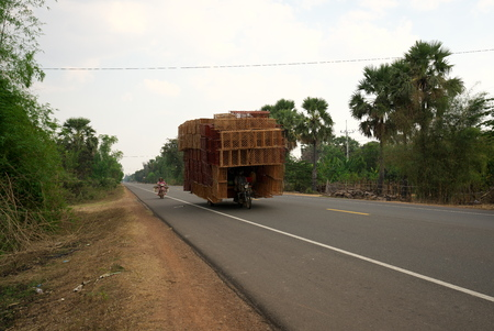 Kampong Thom, Cambodia-January 12, 2019: A motorcycle runs on National Highway 6 in Cambodia loading lots of rattan boxes