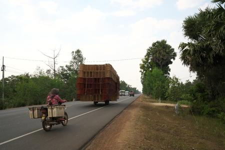 Kampong Thom, Cambodia-Januar 12, 2019: A motorcycle runs on National Highway 6 in Cambodia loading lots of rattan boxes Editöryel
