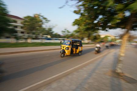 Siem Reap, Cambodia-Januay 9, 2019: A panning of tuk tuk on National Highway 6 in Siem Reap, Cambodia Editöryel