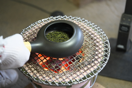 Chiba, Japan-February 19, 2019: Roasting green tea with an earthenware baking pan on Earthen charcoal brazier. Roasted green tea is called Hojicha in Japanese.
