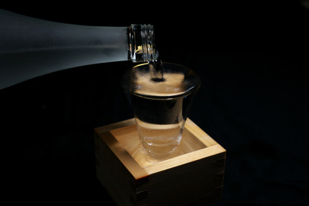 Tokyo, Japan-March 7, 2019: Pouring sake into a glass inside a wooden container for drinking or measuring sake Stok Fotoğraf