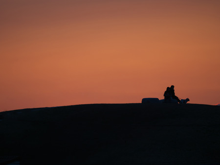 Tokyo, Japan-March 11, 2019: A silhouette of two persons sit on a bench with a dog on a hill at sunset
