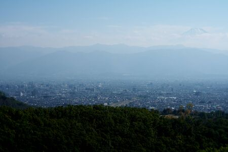 Yamanashi,Japan-November 2, 2019: Panoramic View of Kofu Basin in Japan in Autumn. The Top of Mt. Fuji Seen Behind Mountains. 写真素材