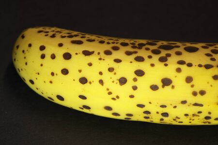 Closeup of a ripe banana with dark spots on black background 写真素材 - 134201596