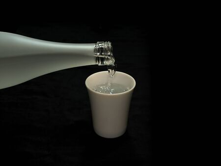 Tokyo,Japan-May 6, 2020: Pouring sake, liquor made from rice, from glass bottle into a cup on black background