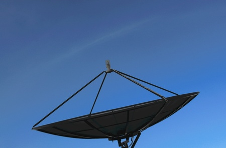 Black satellite dish on blue sky blackground photo
