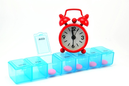 Dialy pill box and red clock on white blackground show medicine time concept
