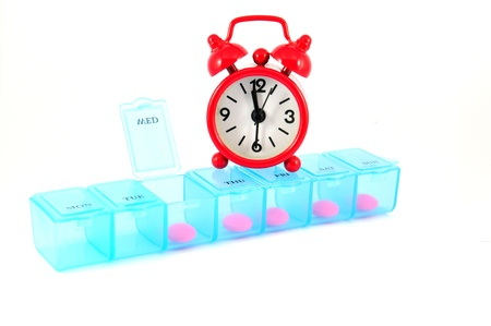 Weekly pill box and red clock on white blackground show medicine time concept Stock Photo - 13639183