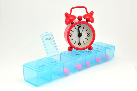 Weekly pill box and red clock on white blackground show medicine time concept Stock Photo - 13639189