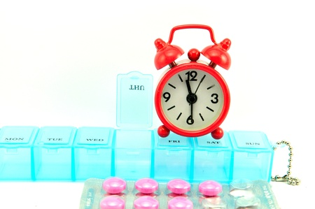 Weekly pill box and red clock on white blackground show medicine concept Stock Photo - 13639188