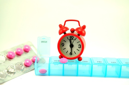 Weekly pill box and red clock on white blackground show medicine time Stock Photo - 13639187