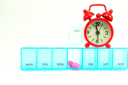 Daily pill box and red clock on white blackground show medicine time concept Stock Photo - 13639185