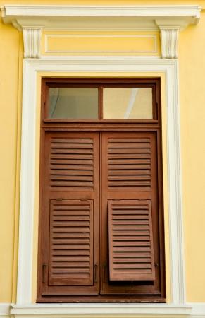 Brown h�lzernen Fensterl�den auf der gelben Wand