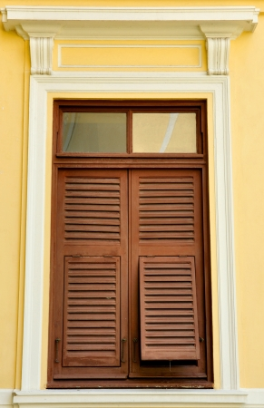 Brown wooden shutters on the yellow wall