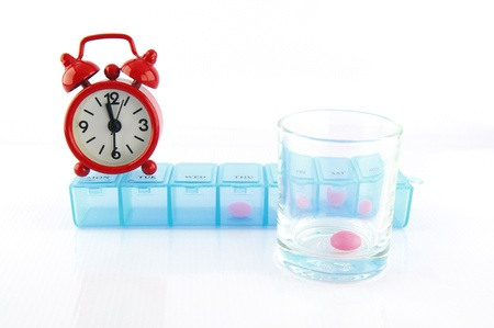Pink tablet and redclok in daily pill box show medicine time Stock Photo - 16654406