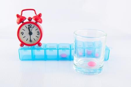 Red clock und verschreibungspflichtige pill box Show Medizin Zeitkonzept
