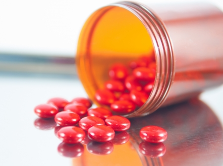 dispensing: Closed up coated red tablet and brown bottle on metal dispensing tray