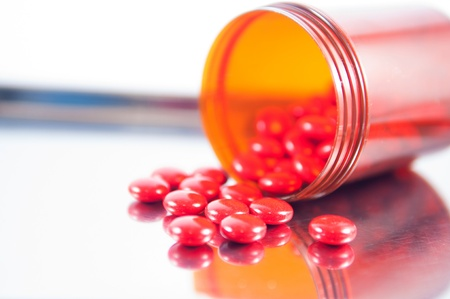 dispensing: Coated red tablet and brown bottle on metal dispensing tray Stock Photo