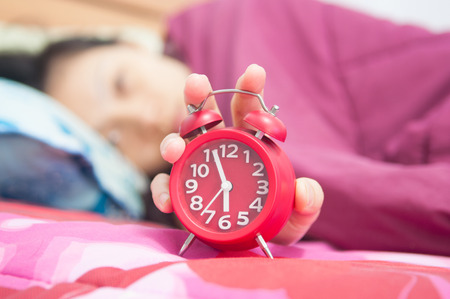 Woman snoozing a red alarm clock  photo