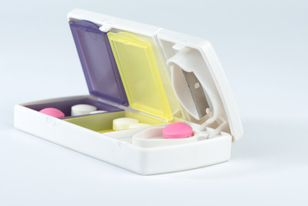pill box: Closed up aluminum blade and pink tablet in pill box