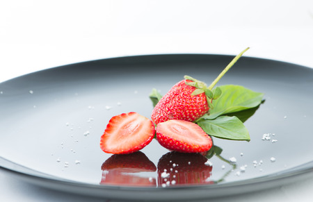 reflex: Fresh strawberry on black dish and reflex