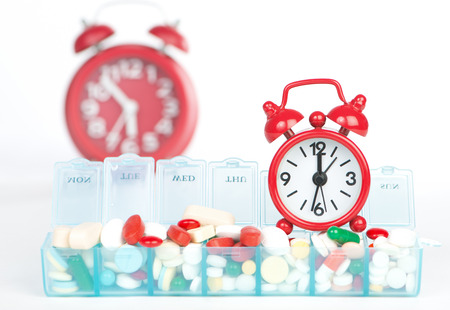 pill box: Red alarm clock and medicine in weekly pill box