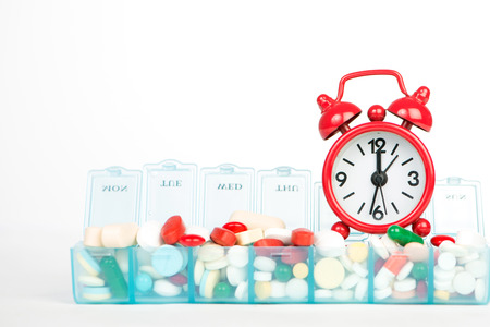 pill box: Medicine in weekly pill box and red alarm clock Stock Photo