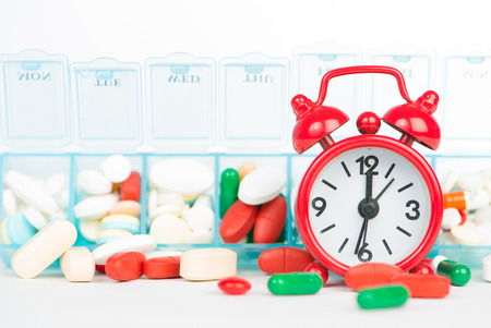 Medicine in weekly pill box and red alarm clock Stock Photo