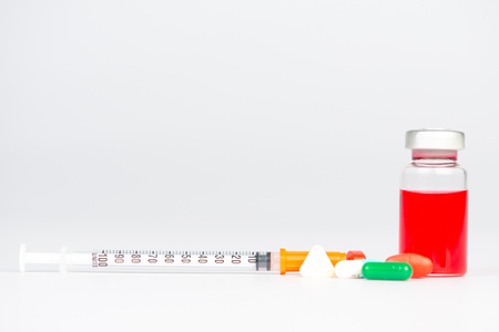vials: Injection vials and medicine tablet on white