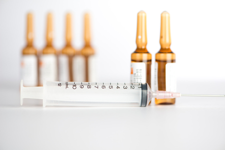 ampule: Injection syringe and brown ampule background Stock Photo