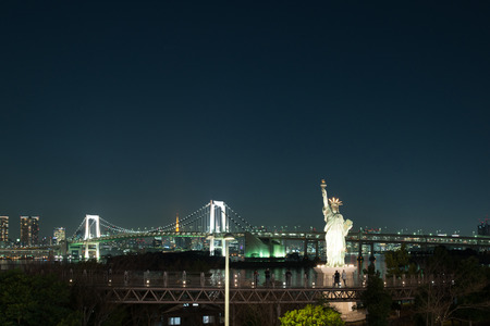 Liberty statue at Odaiba with rainbow bridge in background Tokyo, Japan.