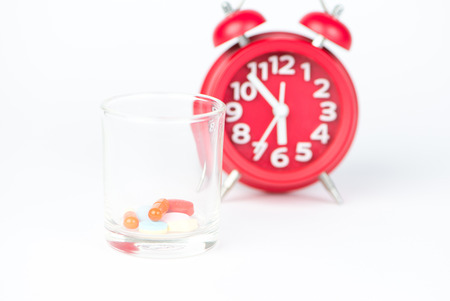 Dispensing glass and red clock show medicine time concept Stock Photo
