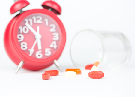 Medicine tablet, dispensing glass and red clock show medicine time