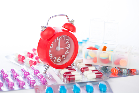 Red alarm clock and medical blister pack show medicine time concept