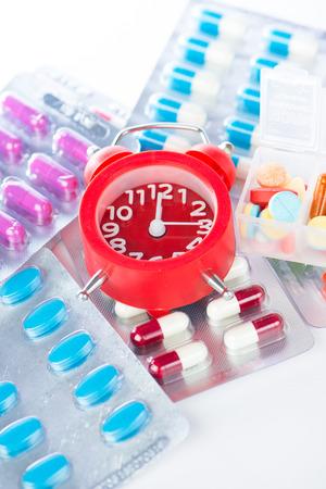 Red alarm clock on medical blister pack