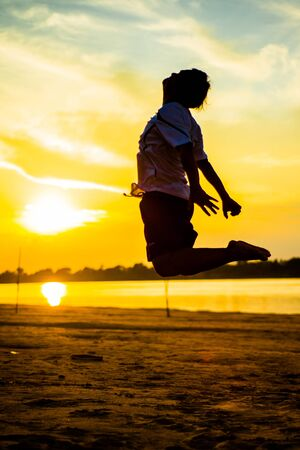 Silhouette picture of Man jumping on beach Stock Photo