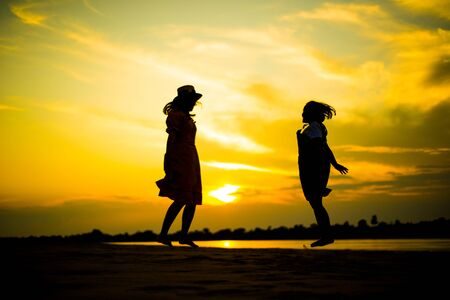 Silhouette picture of girls jumping on beach