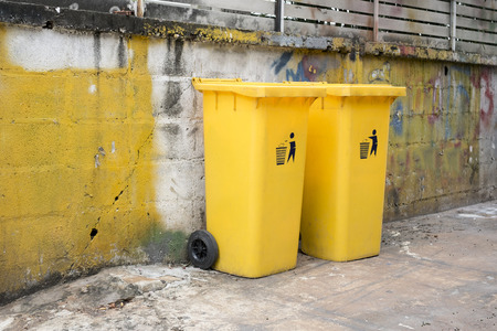 two yellow dustbin at dirty wall