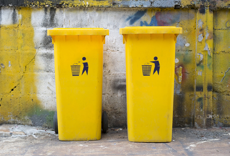 two yellow dustbin at the wall Reklamní fotografie
