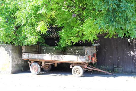 Chariot tracteur Charrette vintage bois garé Geschnitzter Traktor mit Hänger à Wittesheim
