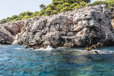 Dubrovnik sea view with the cliff and rocks sea water splashing on the rocks view from the middle of ocean