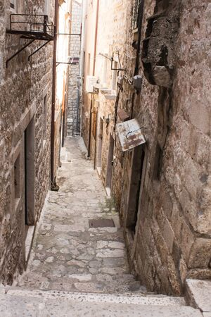 Old city alley, streets, and stairs of Dubrovnik old town, Croatia, Old stone walls on both side, stones on the floor