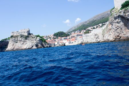 Dubrovnik sea view with the cliff and rocks sea water splashing on the rocks view from the middle of the ocean