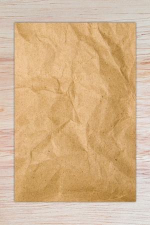 crumpled paper of brown on a wood background Stock Photo