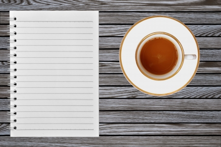 notebook and cup of coffee on wooden background photo