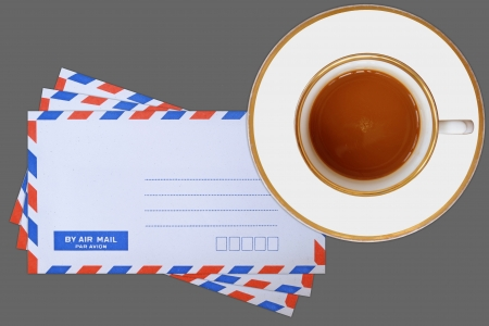 mail envelope and coffee cup on gray background
